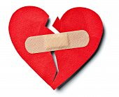 stock photo of breakup  - close up of aplaster and paper broken heart on white background - JPG