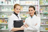 stock photo of antibiotics  - Two cheerful pharmacist chemist woman standing in pharmacy drugstore - JPG