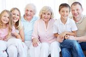 stock photo of grandparent child  - Portrait of senior and young couples with their children looking at camera at home - JPG
