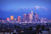 Downtown Los Angeles skyline over snowy mountains at twilight.