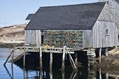 Lobster traps and fishing sheds in the small fishing village and tourism destination of Peggy's Cove, Nova Scotia, Canada. poster