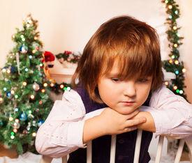 stock photo of sad christmas  - Sad kid sitting with Christmas tree and fire place on the background sad as Christmas is over - JPG