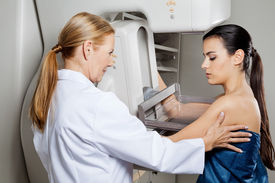foto of mammography  - Mature female doctor assisting young patient undergoing mammogram - JPG