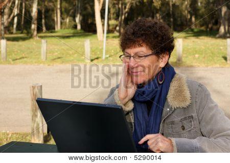 Senior Woman Using Laptop Outside