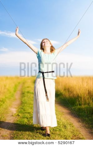 Young Happy Woman Walking On A Field