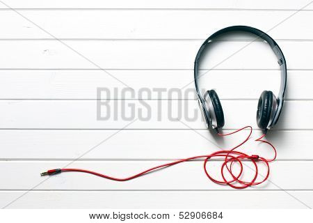 top view of black headphones on white wooden table