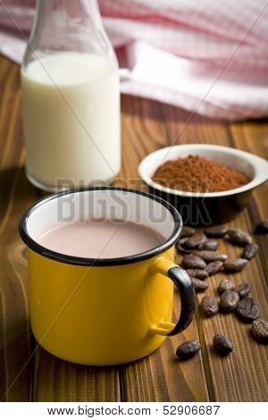 cocoa drink in tinny cup with cocoa beans and powder
