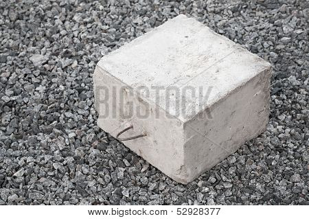 Big Concrete Construction Block With Metal Lug On Gray Gravel