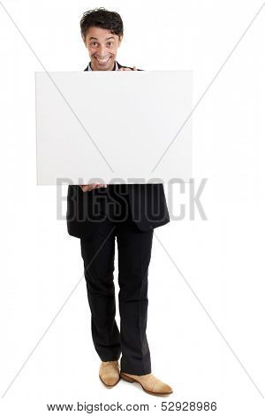 Persuasive middle-aged man with a big smile holding a blank sign in front of his chest as he draws your attention to the copyspace and gives it his endorsement, on white