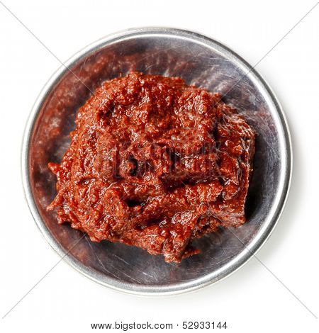 Tandoori paste in small metal dish, isolated on white.
