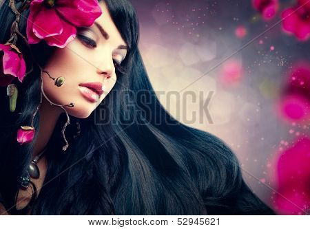 Beauty Woman With Long Black Hair. Beauty Brunette Model Girl Portrait with Big Purple Flowers in her Hair. Hairstyle, Perfect Face Make up. Smoky Eyes Shadows