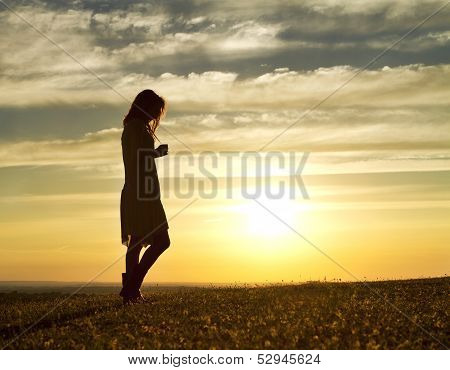 Woman walking alone at sunset