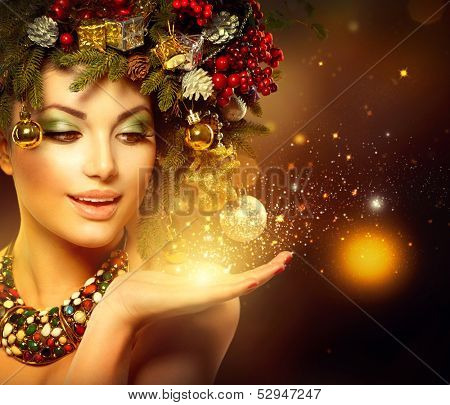 Christmas Winter Woman with Miracle in Her Hand. Fairy. Beautiful New Year and Christmas Tree Holiday Hairstyle and Makeup. Gift. Magic Girl. Beauty Fashion Model over Holiday Blurred Background.