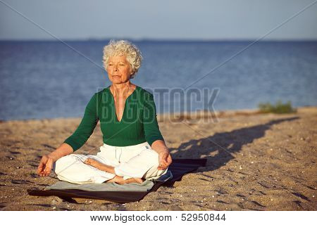 Elderly Woman On Beach Meditating By Ocean