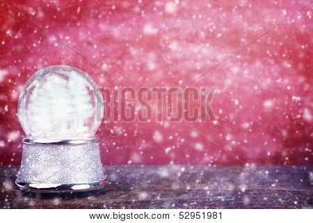Empty Snowglobe Against Red