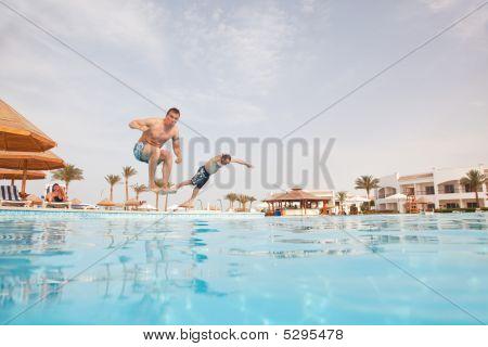 Two Men Having Fun At Swimming Pool.