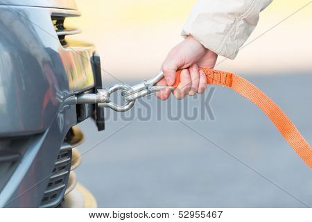 Hand holding tow rope near towing hook assembled to a broken car