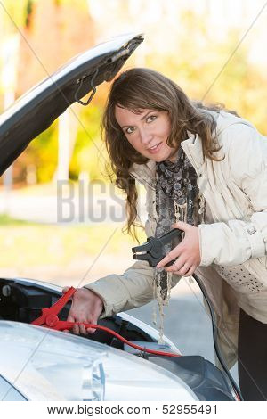 Beautiful woman connecting booster cables to a car battery