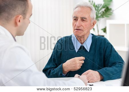 Senior man sits with his doctor and he complained of chest pain