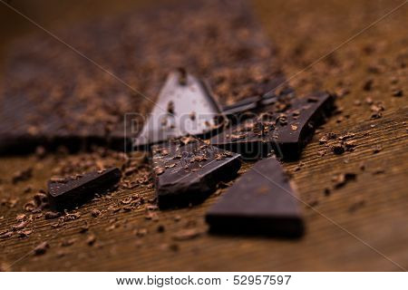 Dark chocolate bar and some powder around it on a wooden surface