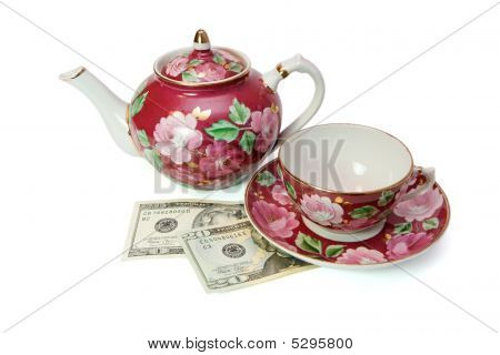 Tea Service Over Dollar Banknotes Isolated