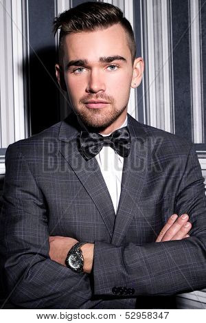 Handsome man with a beard who is wearing a dark suit and a tie is posing over a striped background