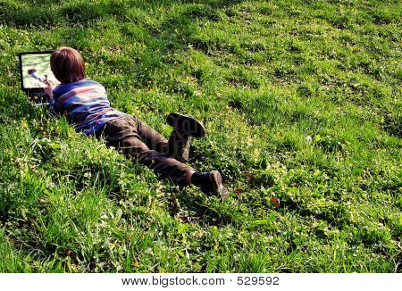 To See Itself. (child With Notebook Lays On A Grass)