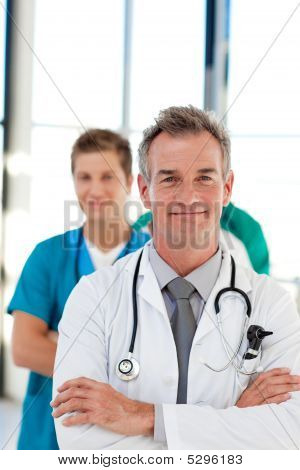 Mature Doctor Leading His Team With Copy-space