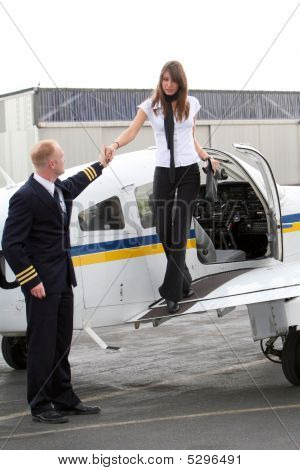 Pilot And Young Woman Get Out Of The Private Plane