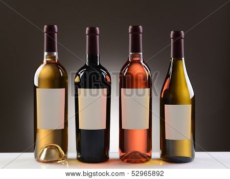 Four Wine Bottles with blank labels on a light to dark gray background. Four different wines including: Cabernet Sauvignon, Chardonnay, Sauvignon Blanc, and White Zinfandel.