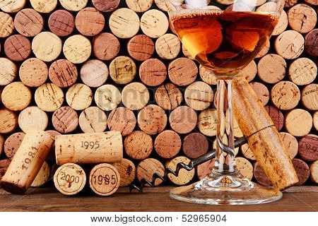Closeup of a wineglass in front of a wall of used corks. An antique cork screw and dated corks are adjacent to the glass. Horizontal format filling the frame.