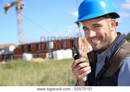 Construction manager on buidling site with walkie-talkie