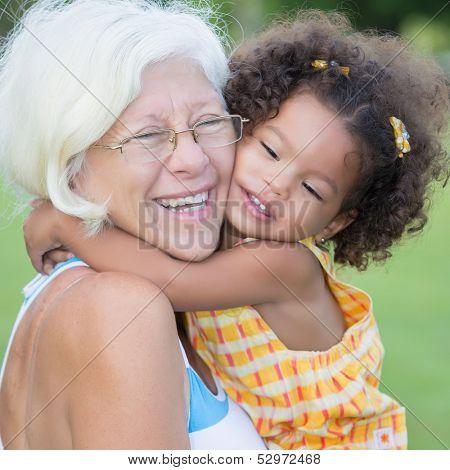 Grandmother hugs her hispanic granddaughter on a park