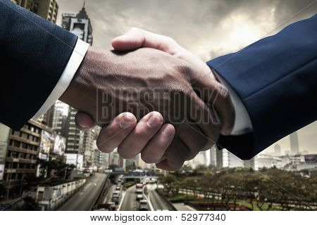 Close up of businessmen shaking hands with cityscape in the background