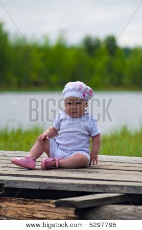 Child Is Sitting On The Timber Flooring Near Lake