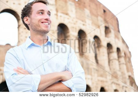 Young casual business man portrait by Colosseum, Rome, Italy. Proud confident happy smiling cross-armed businessman in shirt standing outdoor looking to side. Male Caucasian man in his 20s.