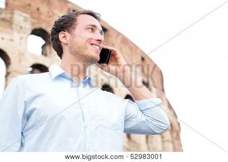 Business man on cell phone, Colosseum, Rome, Italy. Young businessman talking on smartphone outside smiling happy in casual shirt in front of Coliseum. Caucasian male professional in Europe.