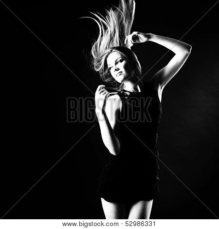 Dancing party girl. Young beautiful excited woman listening music and dancing with long blond hair fly-away, b&w