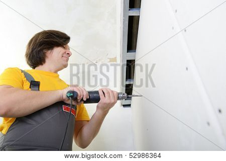 Man using drill to attach drywall panel to wall. Work with plasterboard