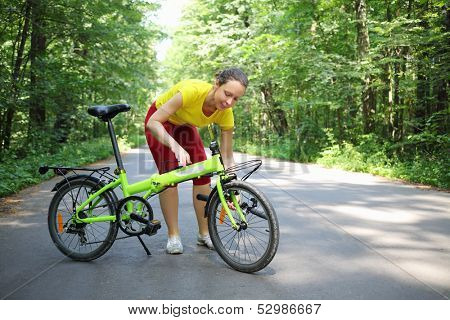Young woman in sport clothes converts bicycle handle bar in park at sunny day.