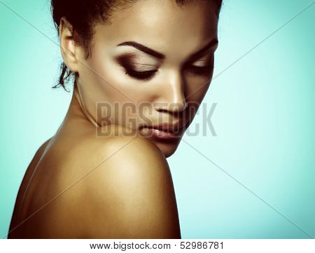 Young mulatto fresh woman with beautiful makeup looking down, isolated on blue, toned