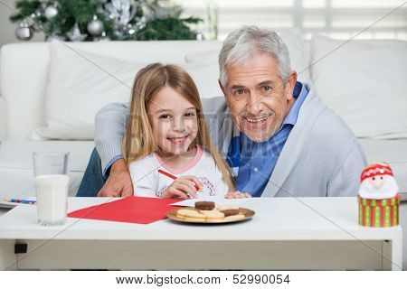 Portrait of happy grandfather and girl with cardpaper sitting at home