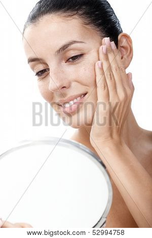 Young smiling woman looking at her face in mirror satisfied.