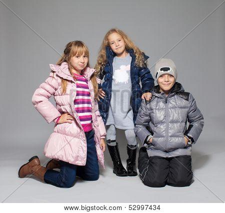 Children in winter clothes. Kids in down jackets. Fashion child