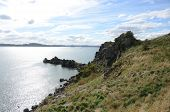 stock photo of promontory  - A view along a rocky promontory on Inchcolm island - JPG
