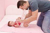 picture of poo  - Young father with modern hairstyle chaning baby diapers - JPG