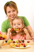 pic of healthy food  - Woman and little girl eating fruit slices on a stick  - JPG