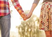 stock photo of jeans skirt  - Young couple in love walking in the autumn park near the river - JPG