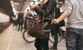 stock photo of unemployed people  - Young woman using mobile phone being robbed by a pickpocket at the subway station - JPG
