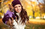 stock photo of miniature pinscher  - Young woman holding her miniature pincher puppy after playing in the park - JPG